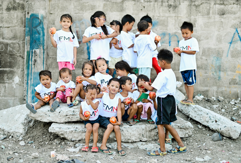 Group of kids wearing FMM shirts and holding food