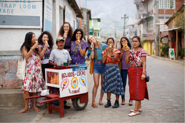 Women eating ice cream in the streets of Guatemala wearing Love Is Project bracelets
