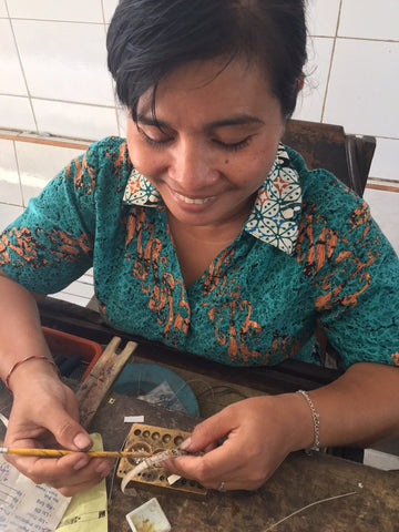 Love Is Project artisan in bali making the love bracelets