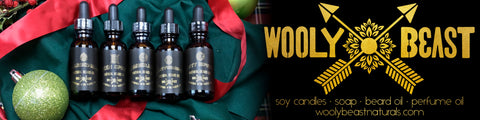 beard oil in amber glass jar with dropper and black and gold label by wooly beast naturals with crossed arrows logo and ornaments and red ribbon