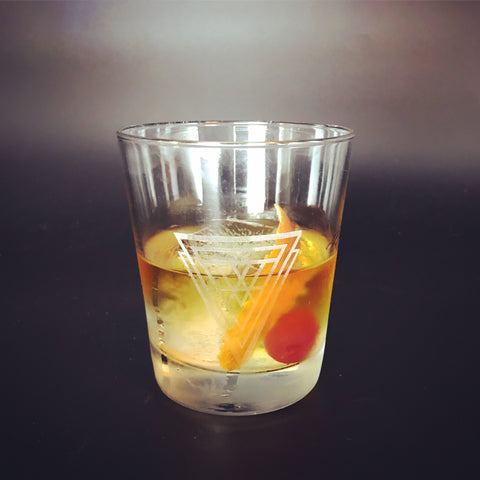 old fashioned cocktail in clear etched glass with sacred geometry sign symbol on it on black background