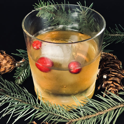 holiday seasonal christmas old fashioned cocktail with cranberries whiskey and pine leaves and pinecones on black background