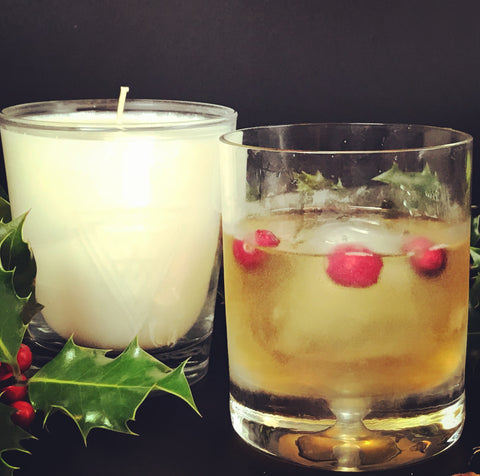 vegan soy wax candle old fashioned christmas with a holiday old fashioned cocktail with cranberries holly leaves and berries on black background