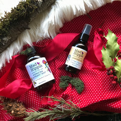 mad hippie advanced skin care cleanser and moisturizer spray on red polka dot holly berries pinecones wood faux fur