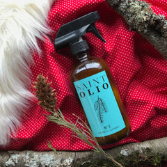 saint olio aromatic cleaning spray in amber glass with pinecones wood and faux fur on red and white polka dot background