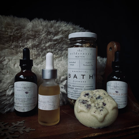 wilderness maven apothocary subscription natural organic wildcrafted artisan handcrafted ticture for health pms facial oils bath lotion bar eco friendly products in moody tones in front of animal sheepskin on a wooden antique table