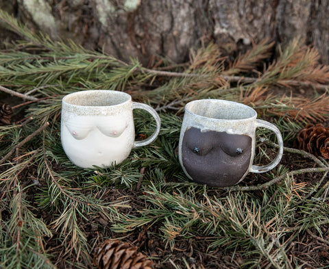 breast bust women feminist empowerment coffee tea mugs in dark and light in front of tree with pinecones and pine leaves under