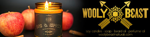 wooly beast naturals banner with black and gold amber glass jar candle big and spicy with apples on black background and logo with crossed arrows