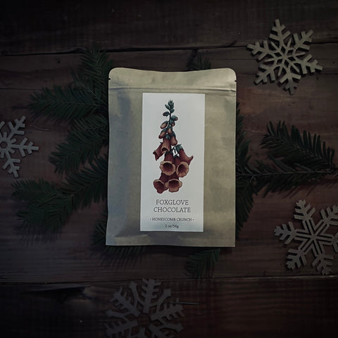 foxglove bag of micro batch chocolate plastic free packaging with a flower on the front in red sitting on an antique wooden table in moody tones with craft paper snowflakes