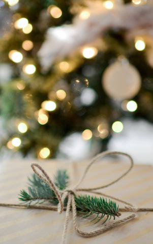 pine needle bunch wrapped in jute string sitting in front of a christmas tree with lights and white ornaments