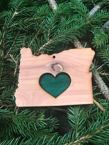 heart in oregon reusable air fresheners smells like pine tree made of cedar wood and sustainable vegan eco essential and fragrance oils on a bed of pine needles by wooly beast naturals