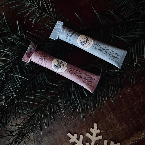 lip therapy organic lip balm in plastic free pink and blue packaging in peppermint and berry flavors sitting on cypress leaves and craft paper snowflakes