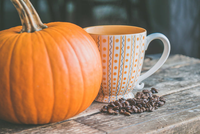 pumpkin on farm table with vintage coffee mug and coffee beans