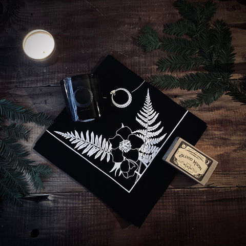 winter solstice gift set collaboration with dark exact and wooly beast naturals with a soy candle lit in a gold tin a fern and moon black and white tarot art altar spread with gold ouiji board natural soap and black snake death candle in a glass jar on top of a antique wooden table laydown moody vibes tones