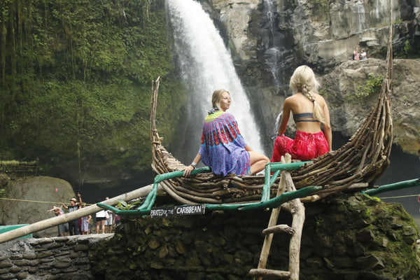 The PIYOGA team sits in front of a waterfall in Bali during their trip to help with ocean conservation.