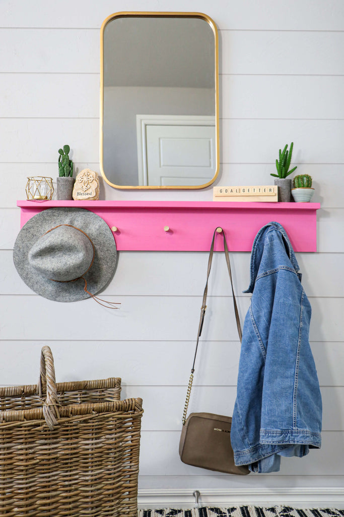 DIY Wall Coat Rack Hanging on a Shiplap Wall under a Gold Mirror with a Hat, purse and jean jacket hanging.