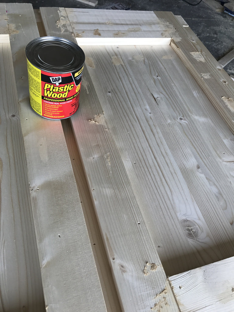 DAP Wood Filler being used on a cabinet for filling nail holes