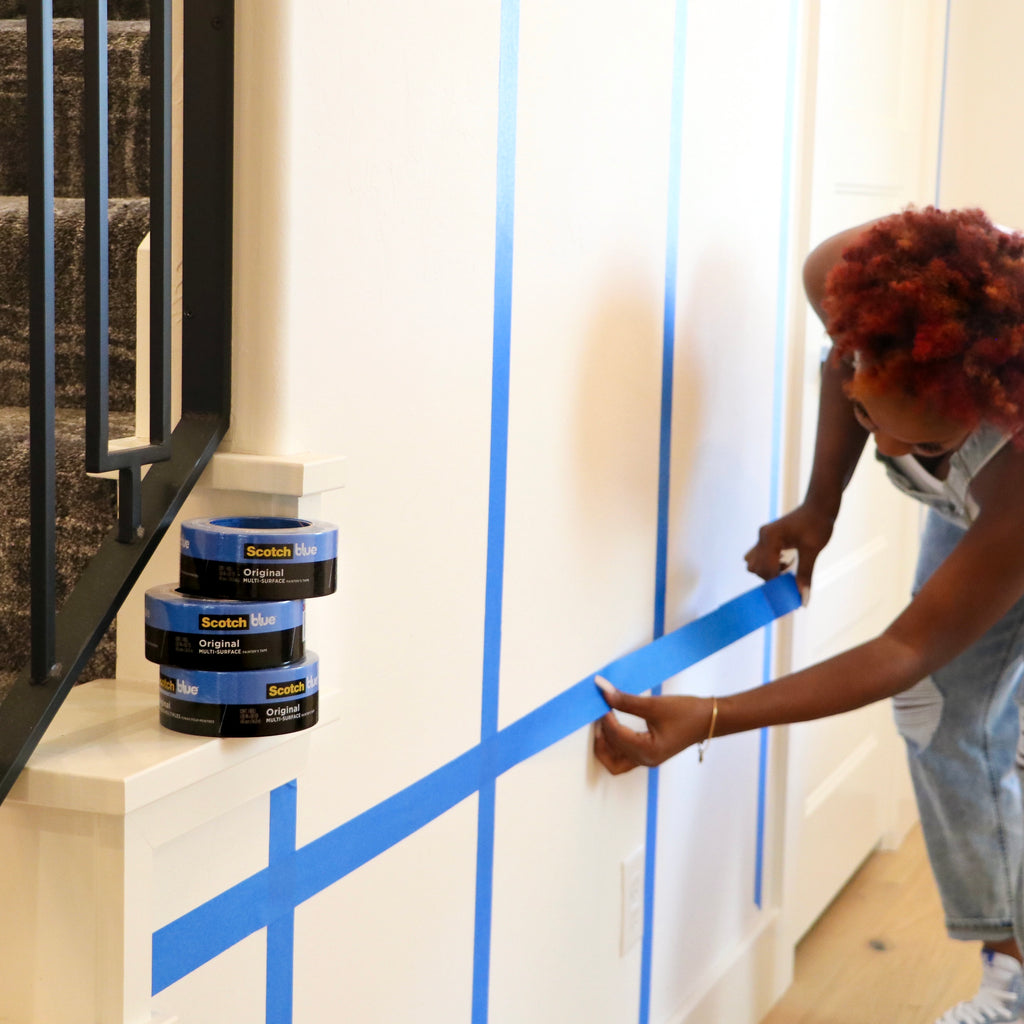 Taping painters tape on wall