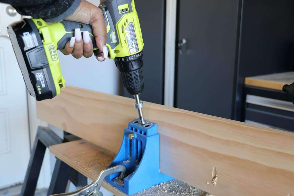Drilling pocket holes into a 1x6 board with a Ryobi Drill and a Kreg Jig