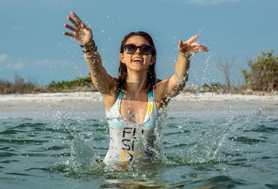 Women in Fuse tank top splashing water in the ocean while wearing sunglasses