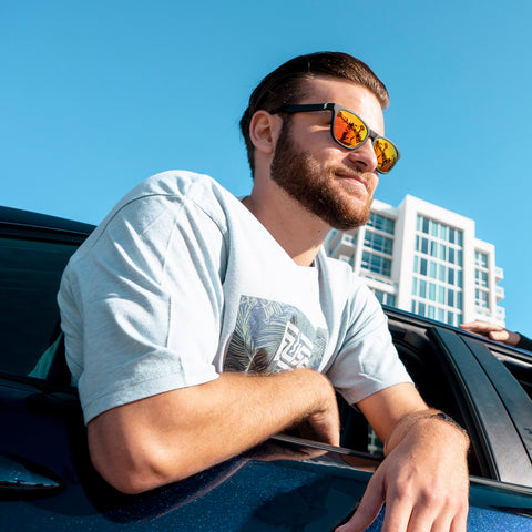 man leaning outside of car window with black sunglasses that have orange lenses