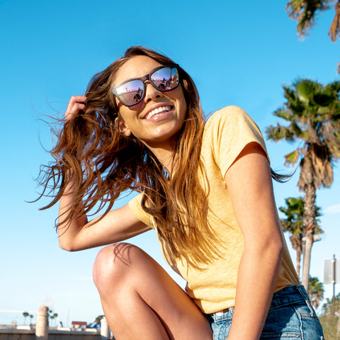 woman kneeling in a yellow shirt with black sunglasses on