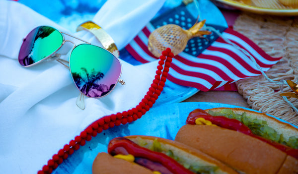 Green mirrored sunglasses next to grilled hot dogs and the American flag in the background.