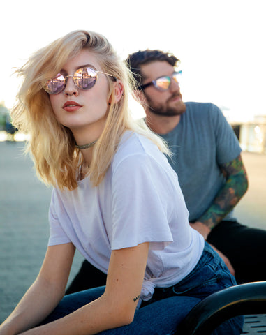Woman and man wearing rose gold sunglasses outside, looking in opposite directions.