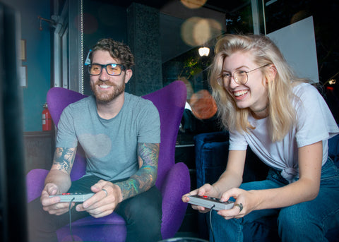 Man and women playing Nintendo Classic while yellow and blue light lenses lenses
