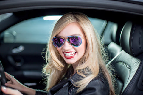Blonde women in a car smiling while wearing a leather jacket and purple mirrored sunglasses.