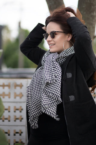 57b07fca23cdf Women in a black coat and black and white checkered pattern scarf wearing  photochromic