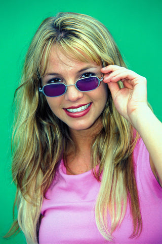 Small oval wired sunglasses were worn a lot in the 1990s. Black and grey lenses were more typical, but colorful lenses were also worn. Like the purple lenses Britney Spears has on her small oval frames.
