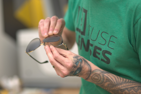 Hands place lenses into a glasses frame