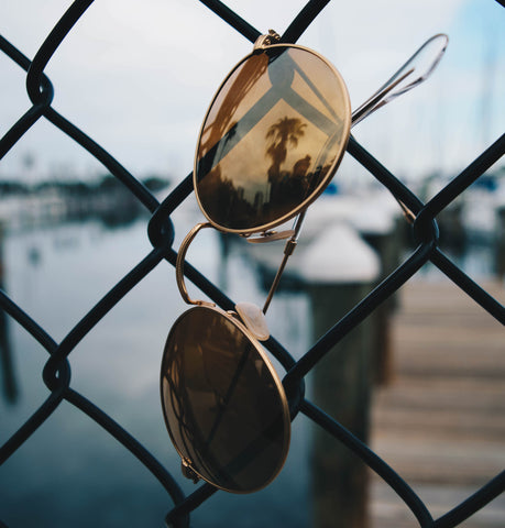 Gold wire frames with a bronze lenses hanging from a fence with a harbor in the background.