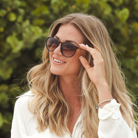 woman in white shirt wearing tortoise sunglasses in front of bushes
