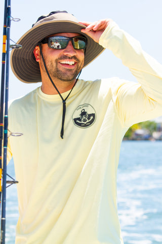 Man smiling with a yellow long sleeve Fuse Lenses shirt and a hat. He is holding a fishing pole and wearing grey polarized sunglasses.