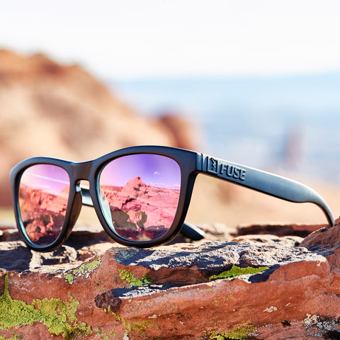 Black Fuse 3 Rocker frames with Rose Gold lenses in a rocky mountain setting.
