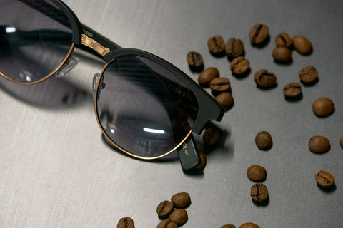 Black frames with light grey lenses and coffee beans scattered all over