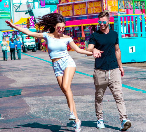 A couple having fun and skipping around the Florida State Fair durning a sunny day while wearing polarized sunglasses.