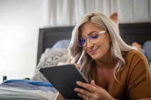 woman on ipad with blue light glasses