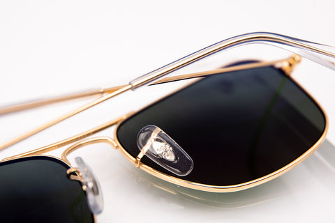 Gold aviator Ray-Ban with dark lenses and a RB engraved under the transparent nose pad