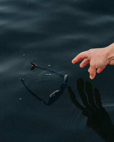 Hand picking up floating sunglasses from the ocean