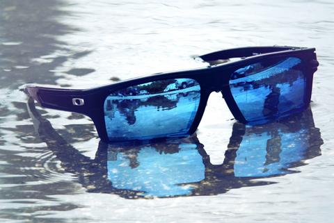 Pair of sunglasses with Glacier mirror lenses from Fuse Lenses sitting in a puddle