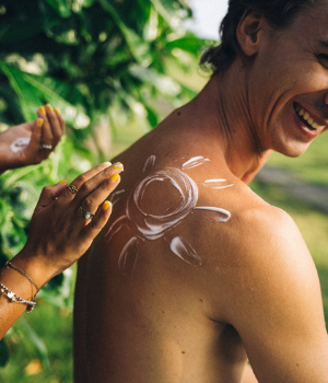 Man smiles as hands apply sunscreen to his back in the shape of a smiley face