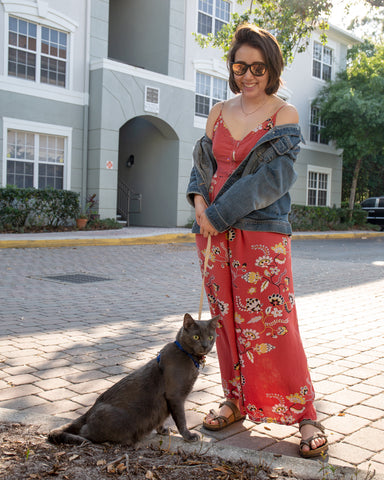 Fuse Lenses employee Alanna outside in front of a building on a stone path with cat Oni