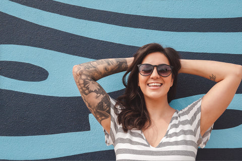 woman up against blue wall wearing black sunglasses