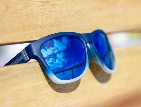 Gradient Blue Sunglasses with Fuse Lenses Glacier Blue Mirror Lenses, on a wooden background.