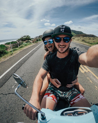 Couple wearing sunglasses riding moped together on scenic road