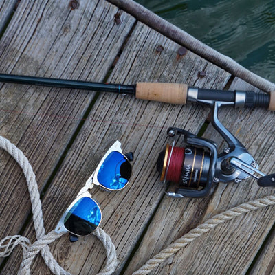 fishing pole and blue polarized sunglasses on a fishing dock