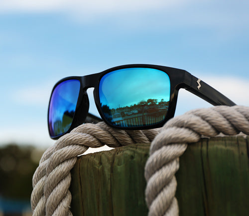 Egmont Fuse Sunglasses with Glacier blue mirrored lenses on a wooden post with rope